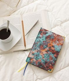Lifestyle photo of the Nebula Orange luxury silk covered notebook by Ana Romero Collection. This notebook is handmade and enhanced with metallic corners, gilded pages and satin ribbon page markers. Click through for more luxury stationery.