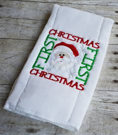 """Soft cotton burp cloth stitched Christmas"""" and a Santa applique face. Personalize this burp cloth with a name below the design. * Cotton burp cloth with polyester inside padding. * Burp cloth finished in the U. Babies First Christmas, 1st Christmas, Christmas Themes, Embroidery Ideas, Embroidery Applique, Machine Embroidery, Christmas Applique, Christmas Embroidery, Burp Cloth Tutorial"""