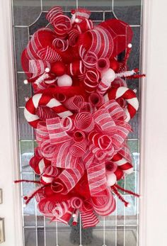 Candy Cane Swag! For this beautiful creation I used a variety of red and white mesh combinations, all of which I purchased from http://www.trendytree.com  used a tinsel garland to make the base of the swag. Then adorned the finished swag with over sized candy canes. https://www.facebook.com/wreathsbyrita #trendytree