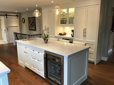 Painted maple cabinetry, Ceasarstone countertops, stainless steel and built-in appliances, kitchen island, apron fronted sink, hardwood flooring