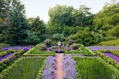 The purple garden is divided into beds edged with miniature rhododendrons and filled with nepeta, heliotrope, and verbena | archdigest.com