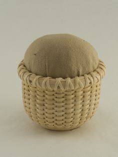 """This precious and perfect pin cushion is functional and aesthetically beautiful to the craft person's eye. It is handwoven from ash and rattan and has a golden tan pin cushion.  You can remove the cushion and store a thimble in the basket if you'd like! 2 1/2"""" Diameter x 3"""" H Imported"""