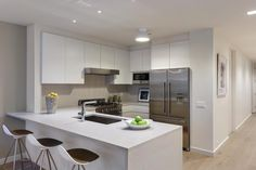 White Italian cabinets pair with high-end stainless steel appliances in this small, simple condo kitchen.