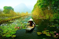A woman paddling down a river full of lily pads on a canoe- Vietnam