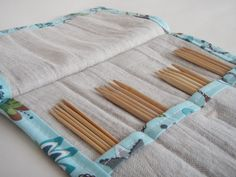 This elegant handmade double pointed knitting needle case will help you organize in style!  Designed to hold four sets of double pointed knitting needles, this mini case is perfect for carrying your favorite needle sizes with you. The main fabric is all natural linen, the trim is a contrasting turquoise blue. A secure flap and sturdy cotton cord keep everything in place.  Simple and elegant, this case is also great for organizing crochet hooks!  The case is approximately 10  high x 3 wide…