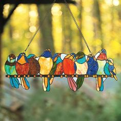 The Stained Glass Birds on a Wire Window Art glows with ambient light to bring elegance to your home. This Tiffany-inspired richly tinted art glass panel showcases 10 multi-colored birds perched on a