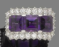 An amethyst and diamond dress ring, by Asprey, 1977 Set with three square step-cut amethysts, within a surround of brilliant-cut diamonds, to a platinum band, diamonds approx. 1.15cts total, maker's mark A, London hallmark