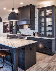 Love this all black cabinetry kitchen! The tall cabinets by the range hood are really beautiful. Great design Love this all black cabinetry kitchen! The tall cabinets by the range hood are really beautiful. Great design Normandy Homes Black Kitchen Cabinets, Kitchen Cabinet Design, Black Kitchens, Cool Kitchens, Tall Cabinets, Upper Cabinets, Kitchen With Marble Countertops, Kitchen Black Appliances, Kitchens With Dark Cabinets