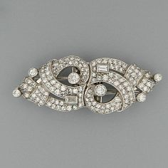 A diamond double clip brooch The openwork geometric design set with brilliant, baguette and single-cut stones.