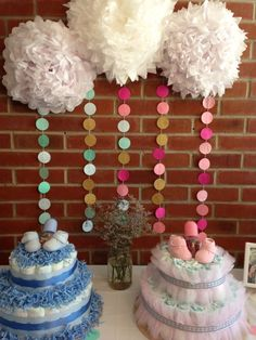 baby shower decoration ideas: DIY circle bunting backdrop, tissue paper poms, and diaper cakes for both a boy and a girl.