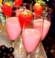 Strawberry smoothies in champagne glasses, garnished with a fresh strawberry. A nice presentation for a special breakfast get-together, a bridal brunch, a shower or Mother's Day. A refreshing non alcoholic alternative. Very pretty for guests to enjoy. ~Photo by Celeste Ivon