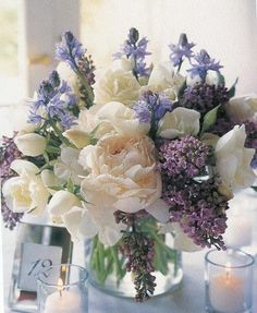 White peonies, purple lilacs, and wildflower centerpiece.