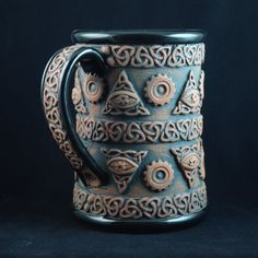 Perk #6 - All-seeing Steampunk Eye Mug - A very limited edition handmade mug. Red clay with black glaze. About 5-1/4 inches (13.5 cm) tall and will hold about 16 fluid ounces (500 ml). Only 25 will be made, each will be numbered. ©2013 Andrew Tarrant - Trespasser Ceramics, All-Seeing Steampunk Eye Mug, Ceramic.