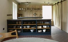 Open shelving, painted blue, provides a backdrop for glassware and tableware. To get the look, seeSteal This Look: A Piggery Turned Kitchen, Custom Larder Included.