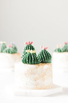 Mini vanilla cakes topped with trios of Swiss meringue buttercream cacti on edible sand.