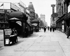 East 14th Street and Fourth Avenue, 1916 In this black and white photo, taken in 1916, the photographer shoots west along the north side of E. 14th Street.  People stroll past the Hotel Rathskeller. A couple of newsies operate a newstand in front of the entrance to the subway.