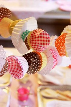 cute party decorations on a budget. Thread colourful patty cake liners, of different sizes, onto string. Hang around your party setup for a cute vintage feel.