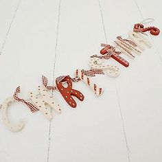 Festive garland that has wooden letters decorated in a variety of festive colours and patterns to spell out 'Christmas'. Each letter measures approx 8cm in height and are strung with hessian string. This garland measures approx 65cm long when hung and has gingham ribbon bows to embellish.
