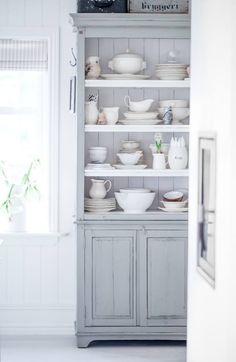 Dish Display - cream color dishes displayed in a simple painted country cabinet - Anettes Hus