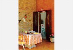Na parede com pintura caiada, o destaque é a porta-balcão de demolição. Ela separa a cozinha do quintal. Do lado externo, detalhes trabalhados em ferro. Dentro, abertura com vidro