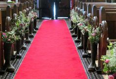 Wellies packed with flowers lining the aisle.