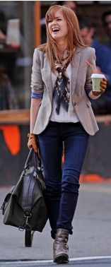 Isla Fisher wearing skinny jeans, ankle boots, a white blouse, beige/tan blazer, and neck scarf with leather driving gloves