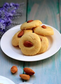 Chinese Almond Cookies - almonds|eggwhite for brushing||Dough:3/4C soft butter|2C flour|2T powdersugar|1/2t bakingsoda|1/2t salt|1egg|2drops vanilla extract - Mix salt&sugar w/butter.Add vanilla.Pour in egg by batch.Ea time,make sure well combined.Mix will be rough.Use hands,roll into round dough.Cover w/plasticwrap&refrigerate30min.Roll dough in long log'divide in sm sections.Roll ea into a sm bowl.Place bowls on bakingsheet&brush eggwhite on.Press 1almond on top of ea cookie.Bake15min@325