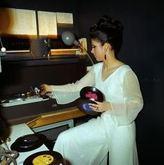 A young female disc jockey or DJ changes a selection of records on twin turntables in a night club in 1967.