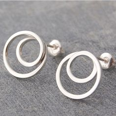 Fashioned from a single square silver wire, these quirky handmade Silver Spiral Stud Hoop Earrings are wound into the form of a swirling metallic vortex. A unique and very modern accessory! #Otisjaxon #Jewellery