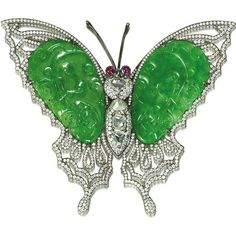 A jadeite, ruby and diamond brooch Designed as a butterfly with antenna en tremblant, the thorax set with hexagonal-shaped rose-cut diamond, the abdomen set with triangular and square shaped rose-cut diamonds, surrounded by brilliant-cut diamonds, the wings set with bright green jadeite with good translucency, carved with bat, money and lingzhi fungus, in a brilliant-cut diamond outline, to collet-set cabochon ruby eyes.