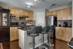 Maple cabinets and a huge corner pantry offering loads of counter and storage space. Diamond Realty & Associates Ltd. Corner Pantry, Maple Cabinets, Large Family Rooms, Basement Bedrooms, Selling Real Estate, Private Room, Floor Finishes, Gas Fireplace, Laminate Flooring