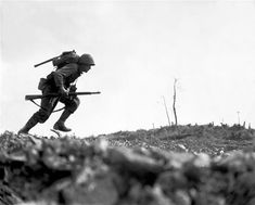 A Marine dashes through Japanese machine gun fire while crossing a draw, called Death Valley by the men fighting there. Marines sustained more than 125 casualties in eight hours crossing this valley. Okinawa, May 10, 1945. Pvt. Bob Bailey.  (Marine Corps)
