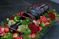 Fles wijn verwerkt in een bloemstuk.  Zowel iets voor de gastvrouw als voor de gastheer.   Fles mag zelf gekozen worden ...