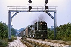 South of Walton KY, a Southern manifest train has a good roll on as it passes under one of Southern's home fabricated signal bridges on the CNO&TP. July, 1980 photo by Mark Hinsdale