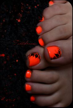 fluorescent nail paint to toe: bright orange and black floral patterns.
