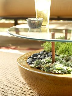 Side table made from glass resting on posts in a planted pot | BHG