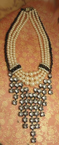 What a great combination of soft white faux pearls and huge rhinestones dripping down from this fabulous necklace set. Worn together they are one of a kind and worn separate they are dramatic and sexy. The pearl necklace measures 15 long on the shortest strand and has pearls that go up to 1/2. The black necklace measures up to 22 1/2 long and the bib measures 3 3/4 at its longest fringe drop. Ask about our ten percent off special before you buy, it could save you a lot of mo...