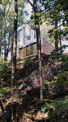"""L'architecte Greg Dutton a conçu cette habitation hors réseau, semblable à une cabane dans les arbres, sur la propriété de sa famille dans la campagne de l'Ohio pour qu'elle soit durable et en phase avec la nature environnante. The Hut se trouve au milieu d'une zone boisée sur une rive surélevée qui surplombe un lac. L'habitation de 56 mètres carrés a été façonnée par son cadre naturel et la relation que Greg Dutton a avec la terre. """" Nous possédons et travaillons la terre depuis plus de…"""
