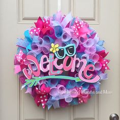 This brightly colored deco mesh wreath will be the perfect way to welcome guests into your home this Summer! This is a large, full wreath measuring 24 in diameter with a depth of 8. The wreath is very colorful and constructed out of hot pink, light pink, light blue and white