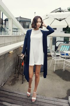 Cute windy summer look with the white dress, navy cardigan, white ankle strap heels, and a cute bob.