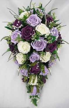 BRIDES SMALL TEARDROP STYLE WEDDING BOUQUET IN IVORY, PURPLE AND LILAC ROSES