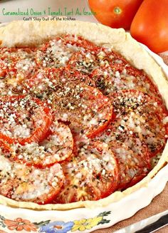 Lots of caramelized onions atop homemade pie crust, topped with four cheeses, a layer of sliced tomatoes, several delicious herbs, with more cheese on top.