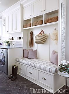 Lovely Showhouse Kitchen | Traditional Home - Laundry & Mudroom by Kim Zimmer  The laundry and mudroom are high-functioning spaces that include the house's back entrance, so Kim Zimmer divided the long, narrow space into zones based on usages. Near the door is a built-in bench with storage drawers, cubbies, and hooks for coats, hats, and bags. A durable wood-look tile floor from Cerdomus stands up to daily traffic in this 24x8-foot room.