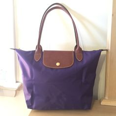 """Longchamp Purple Small Le Pliage Shoulder Bag Details & Care LIKE NEW! Embossed leather trims a water-resistant nylon tote that folds into a compact shape for storage. Top zip closure with outer snap tab. Interior wall pocket. Water-resistant lining. Folds flat for storage. Nylon with leather trim. By Longchamp; imported. 10""""W x 9 ¾""""H x 5 ½""""D. (Interior capacity: medium.) 8"""" strap drop. .5 lbs. Longchamp Bags Shoulder Bags"""