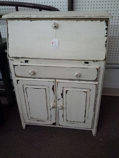 SOLD - This petite drop front desk has a single drawer and double doors for storage. Cubbie space in the desk. It has been painted white, distressed and finished with a dark wax. It measures 28 inches across the front, 14 inches deep and stands 39 inches tall. It can be seen in booth D 16 at Main Street Antique Mall 7260 East Main St ( E of Power Rd ) Mesa 85207  480 9241122open 7 days 10 till 530 Cash or charge 30 day layaway also available