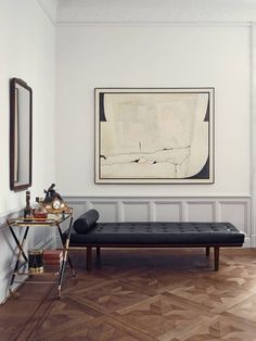Set and prop stylist Joanna Lavén does away with color almost completely inside her Stockholm, Sweden apartment — a black leather daybed complements the muted palette.