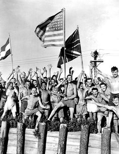 Allied prisoners of war cheering their rescuers, and waving the flags of the United States, Great Britain and The Netherlands as the U.S. Navy arrives at the Aomori prison camp, near Yokohama, Japan, on 29 August 1945.