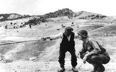 Robert Capa, ITALIA. 4-05 Agosto 1943. Contadino siciliano indica ad un ufficiale americano verso dove si sono diretti i tedeschi.