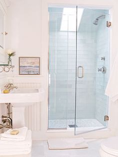 Old meets new in this Sag Harbor, New York, cottage bathroom. A built-in medicine cabinet, pedestal sink, and beaded-board wainscoting add vintage charm, while modern touches include marble floors, a skylight, and a large shower with glass doors and glass subway tiles. myhomeideas.com