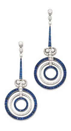 A pair of Art Deco of sapphire and diamond pendent earrings, 1920s. Each of annular design, set with calibré-cut sapphires and circular-cut diamonds, post fittings.